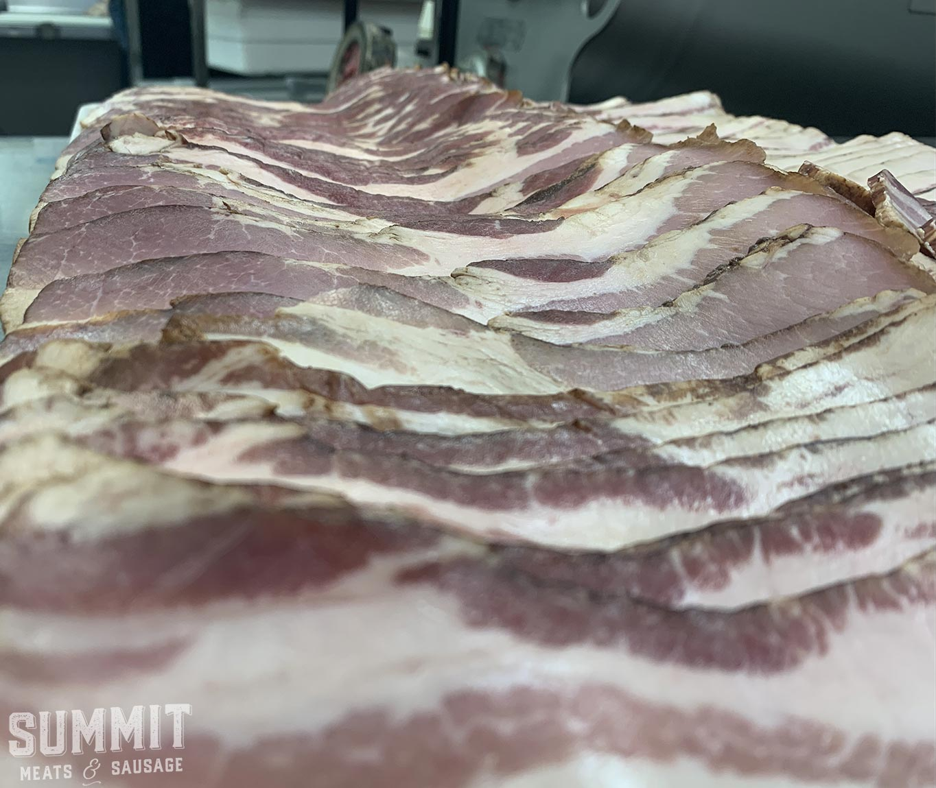 Shot of a bunch of bacon lined up on a tray at Summit Meats